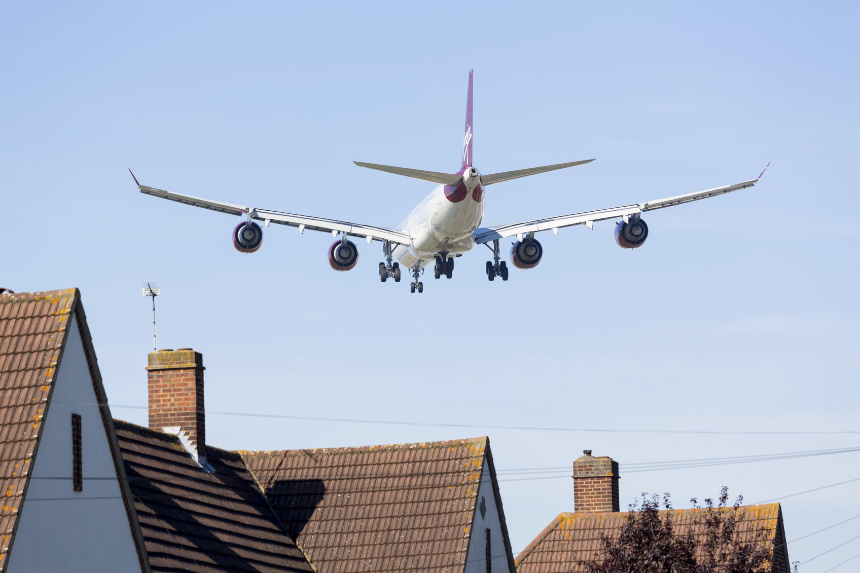Heathrow Airport, London, England - September 9, 2012: Virgin Atlantic Airbus A340 approaches Heathrow Airport flying low over homes near the runway