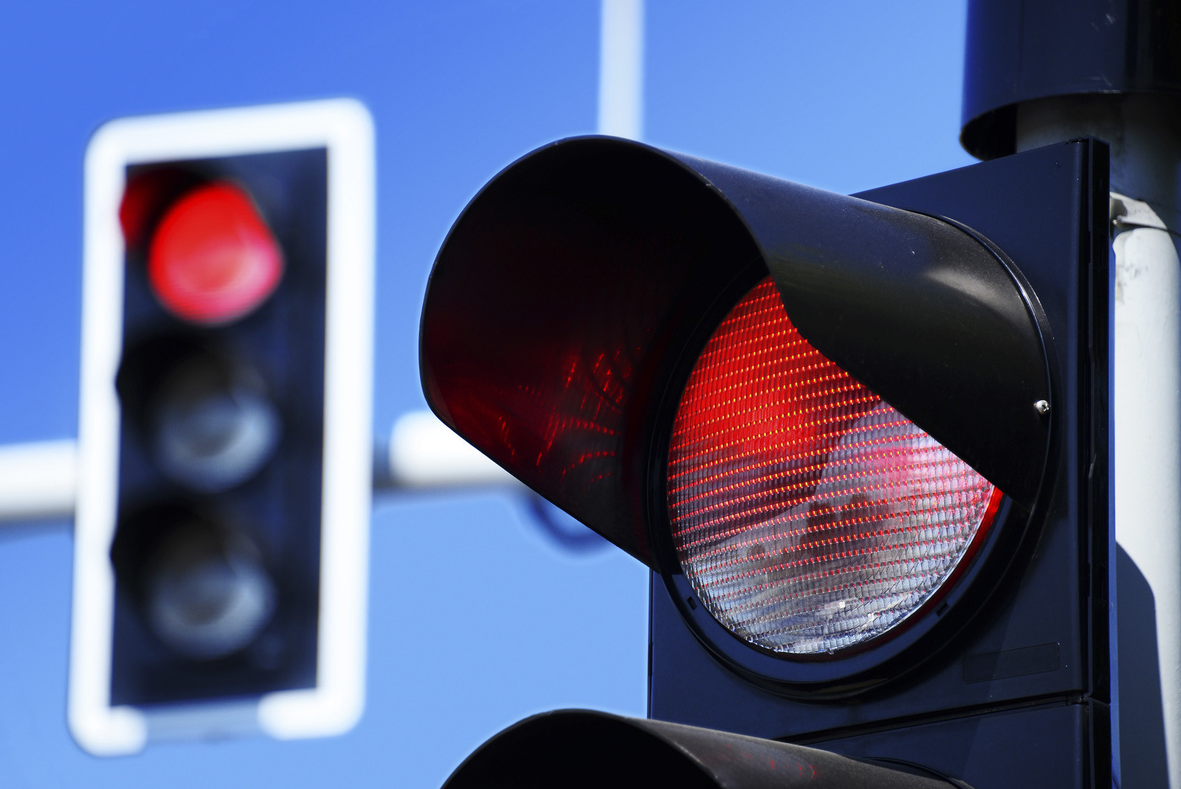 Traffic lights over blue sky. Red light.