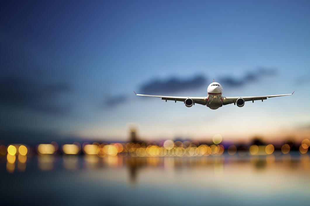 Avión aterrizando en una pista al atardecer, de frente