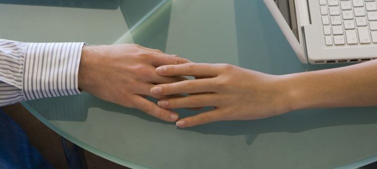 Couple touching hands by laptops