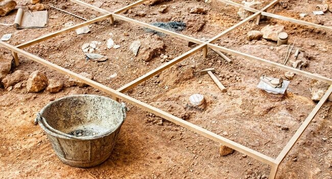 excavación arqueológica con líneas para marcar zonas y útiles como martillo, pincel o cubo