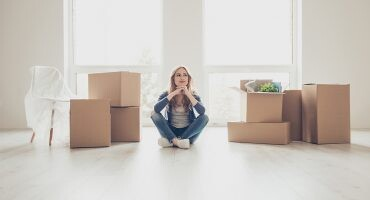 mujer sentada en su vivienda de alquiler