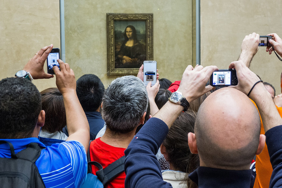 tourists taking a photo of the mona lisa