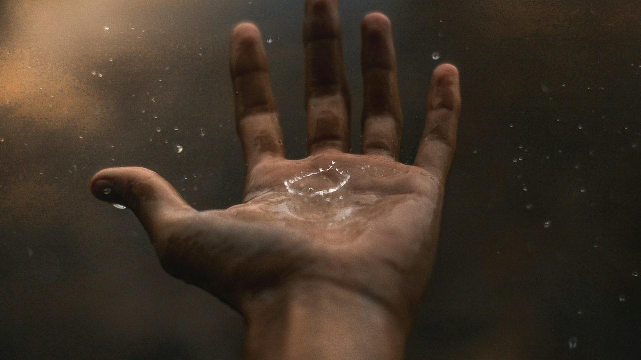 mano gota agua