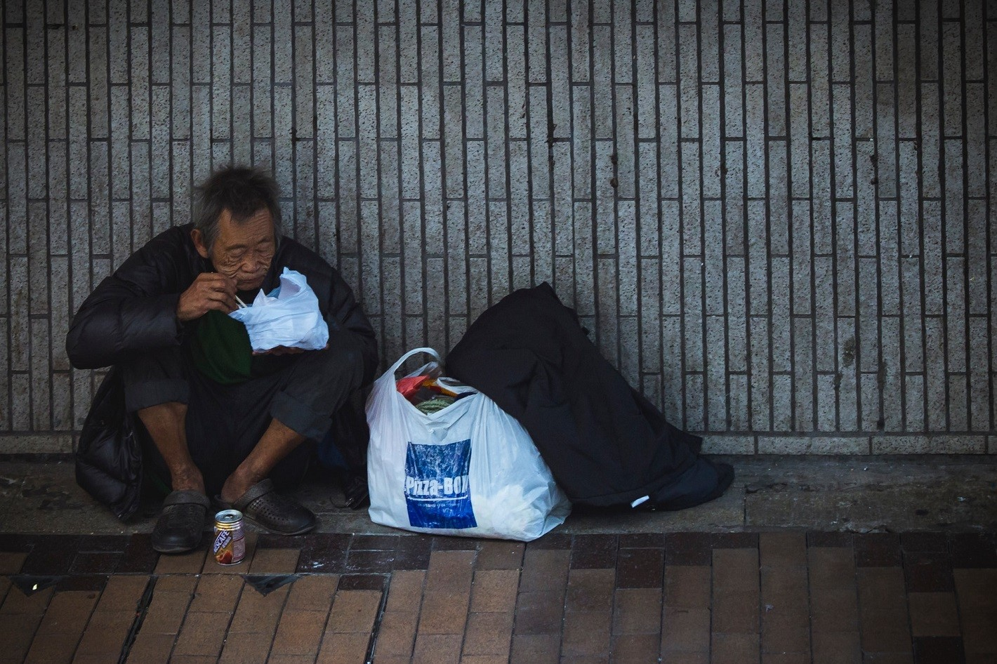 homeless man eating in the street