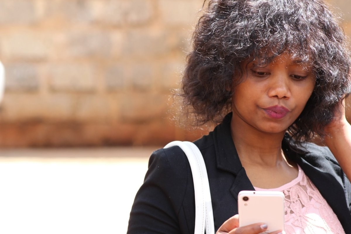 african woman checking her phone