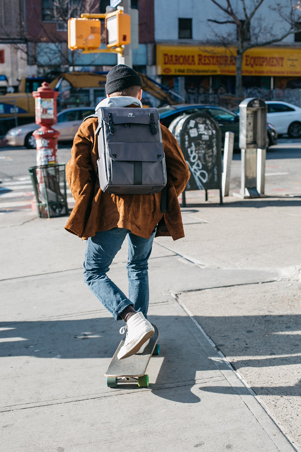 young man with a backpack riding a skateboard