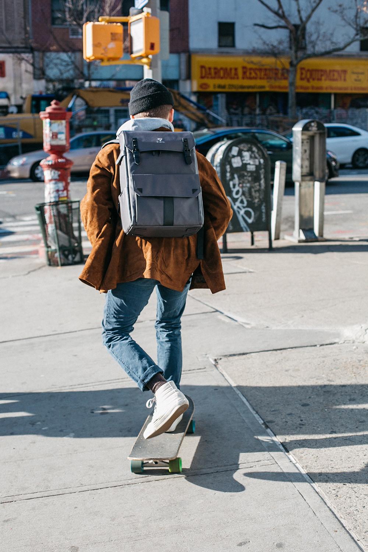 persona en monopatín con una mochila a cuestas