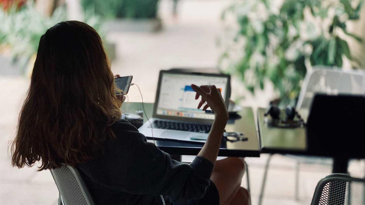 Una mujer atiende al mismo tiempo a su móvil y a su ordenador portátil.