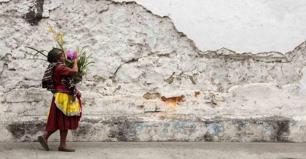 Una mujer indígena pasea con un ramo de flores en Guatemala..