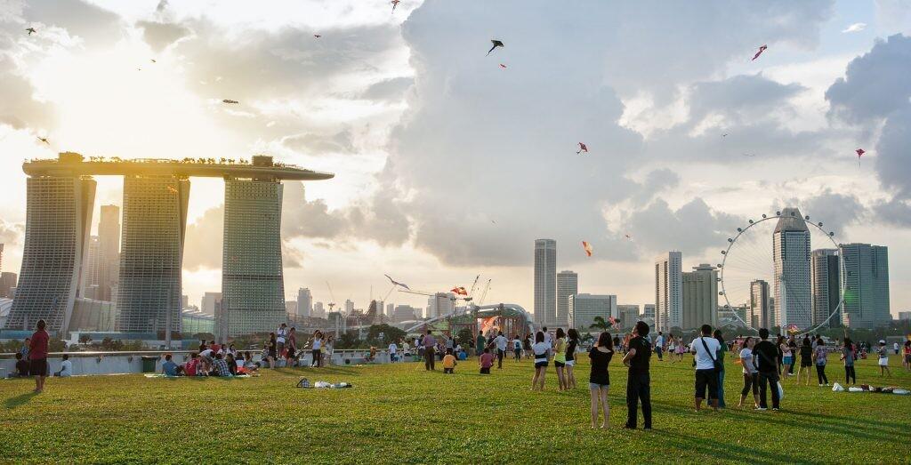 parque de Singapur en el que una muchedumbre vuela cometas al atardecer