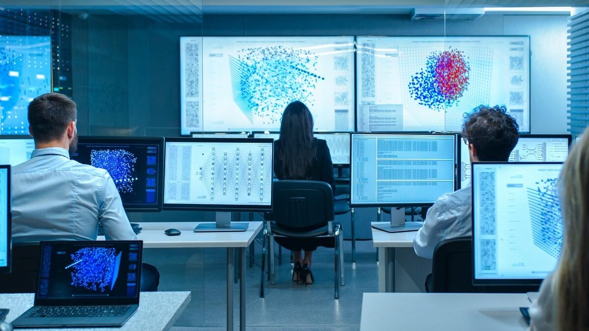 Personas trabajando en una oficina con ordenadores mostrando datos