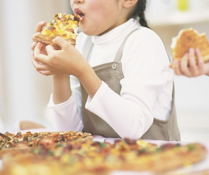 A Young Girl eating a pizza